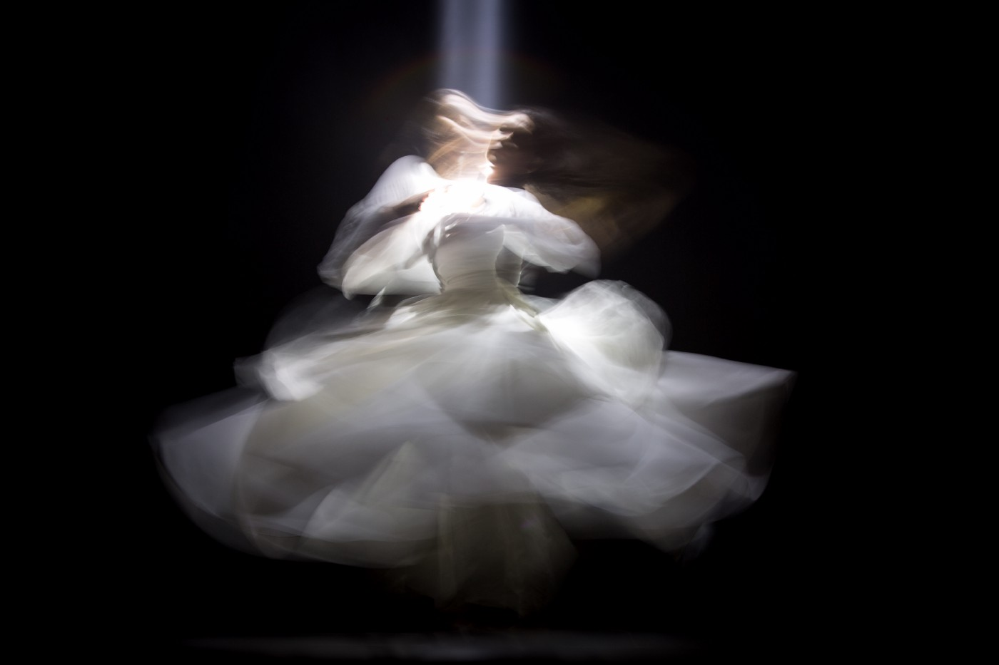 Image is that of a female dancer in a white full skirted gown and she is twirling around so that the image of the skirt is not sharp. From above there is a light shining down on the head of the dancer.