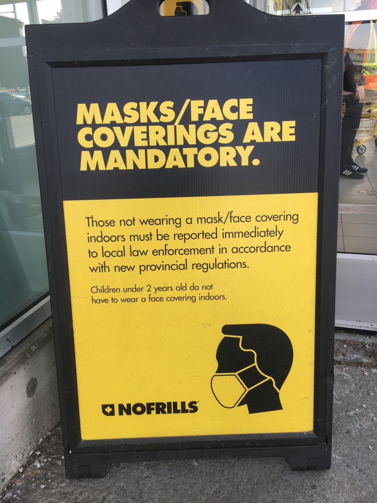 """A """"Masks/face coverings are mandatory,"""" sign at a local No Frills supermarket in Pickering, Ontario"""