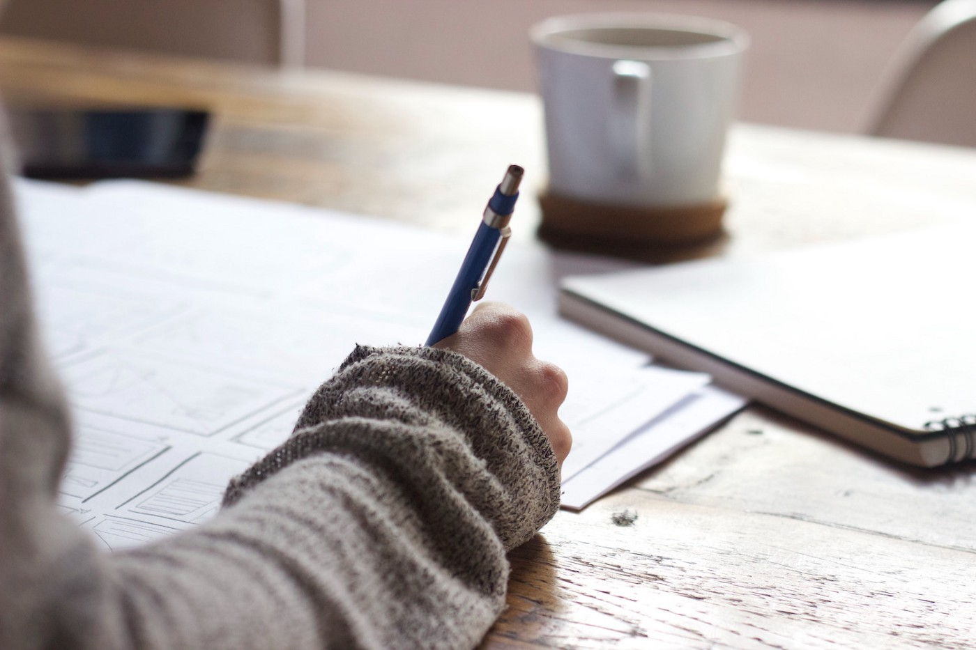 Photo of a person sketching in a notebook next to a cup of coffee.