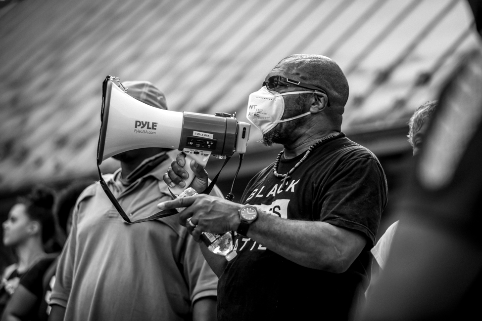 A masked and protesting Don Gathers holding a megaphone.