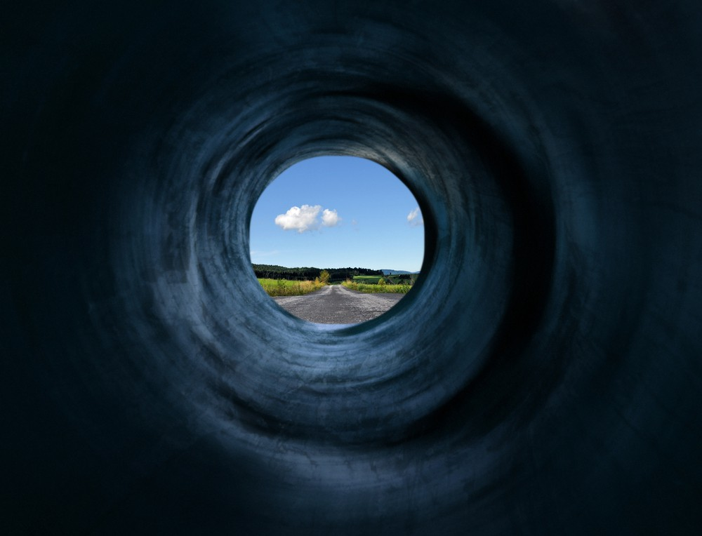 Photograph of a scene through a tunnel. The image indicates how one cannot see the entire picture through a tunnel indicating how stress impacts creativity by making us tunnel-visioned.