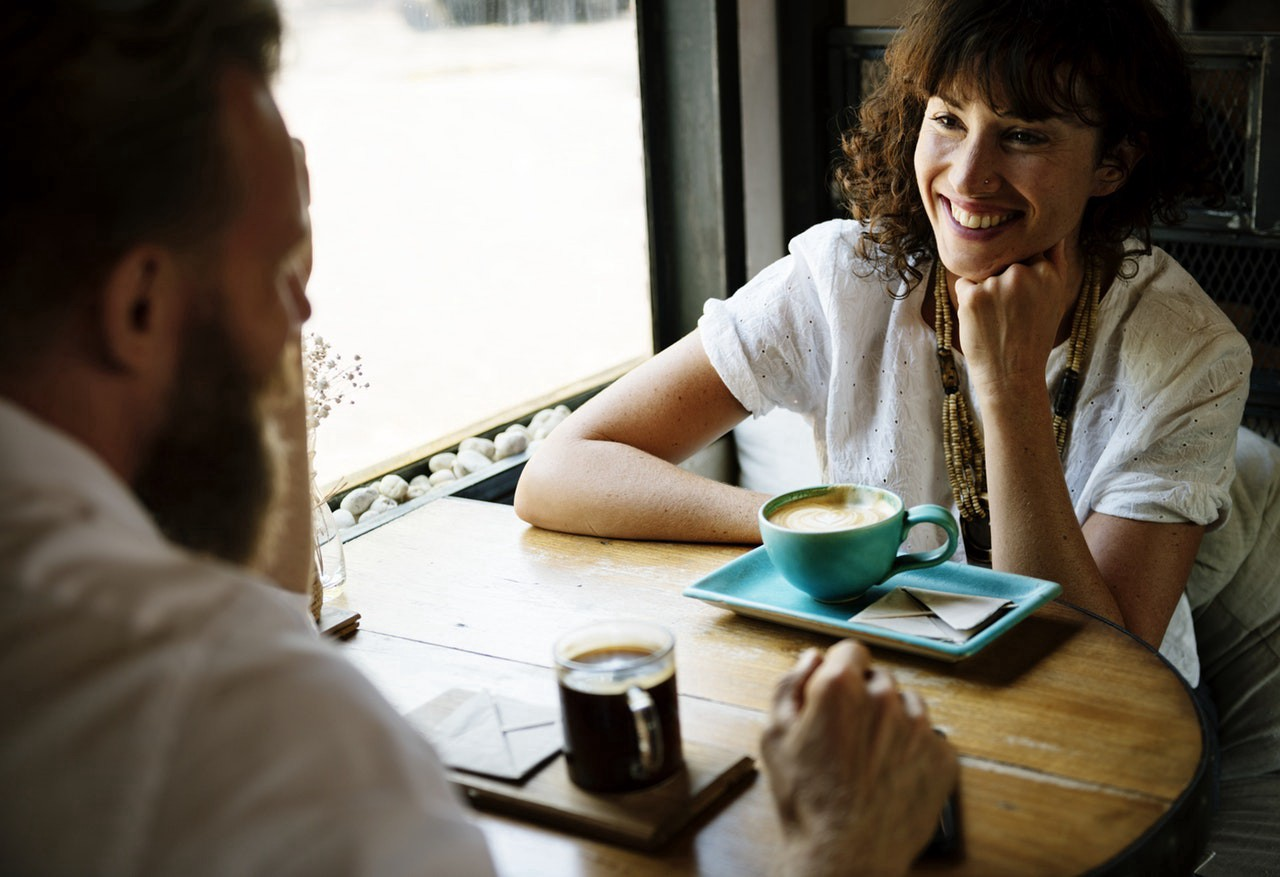 Man (left) and woman (right) in a conversation in a cafe