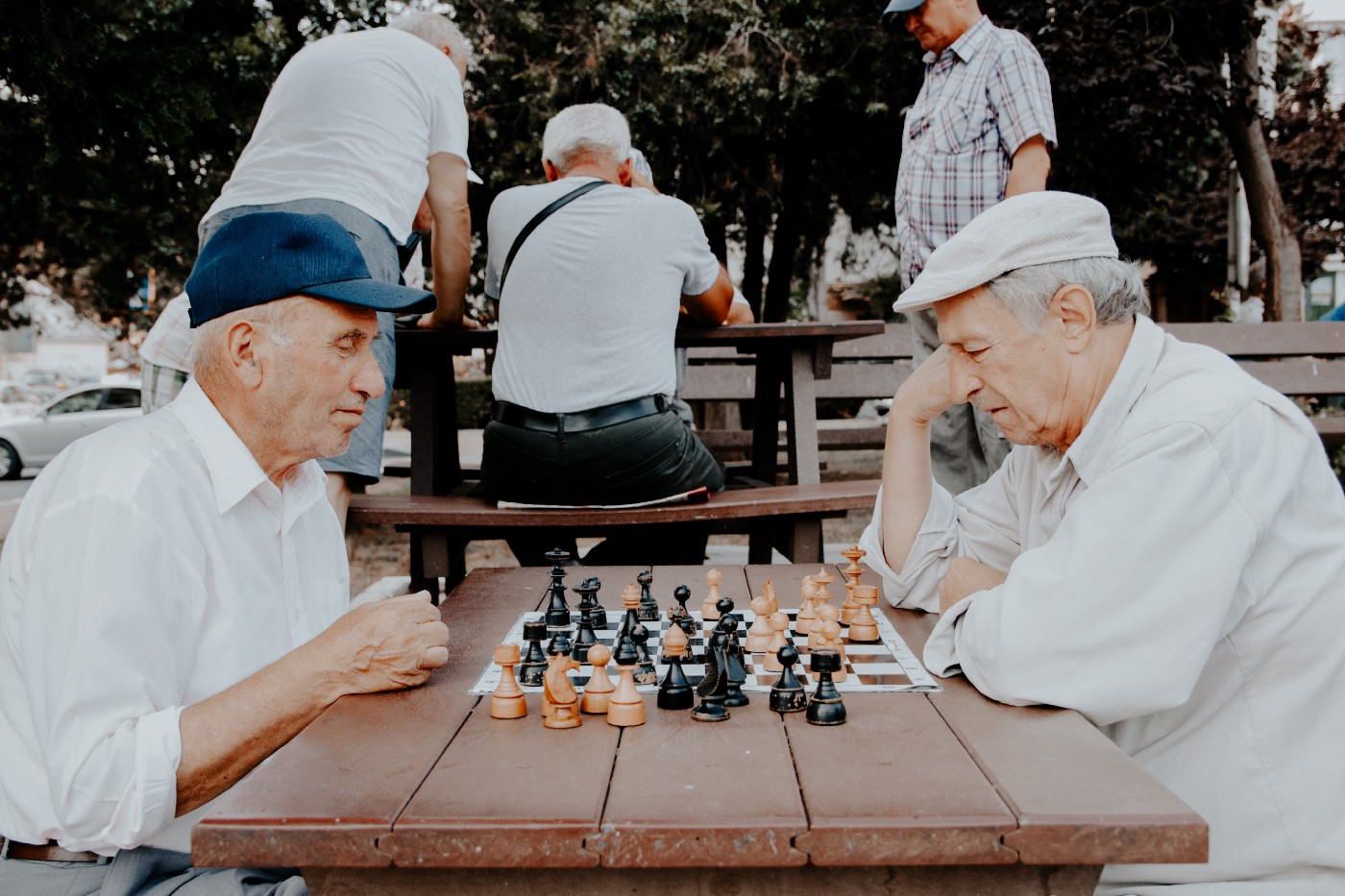 Two old men playing chess at a park