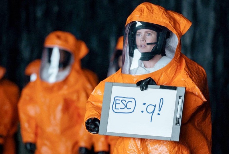 """Amy Adams is holding a sign in an attempt to communicate with aliens in the film """"Arrival"""", but instead of showing the word """"Human"""" it shows the command to exit Vim"""