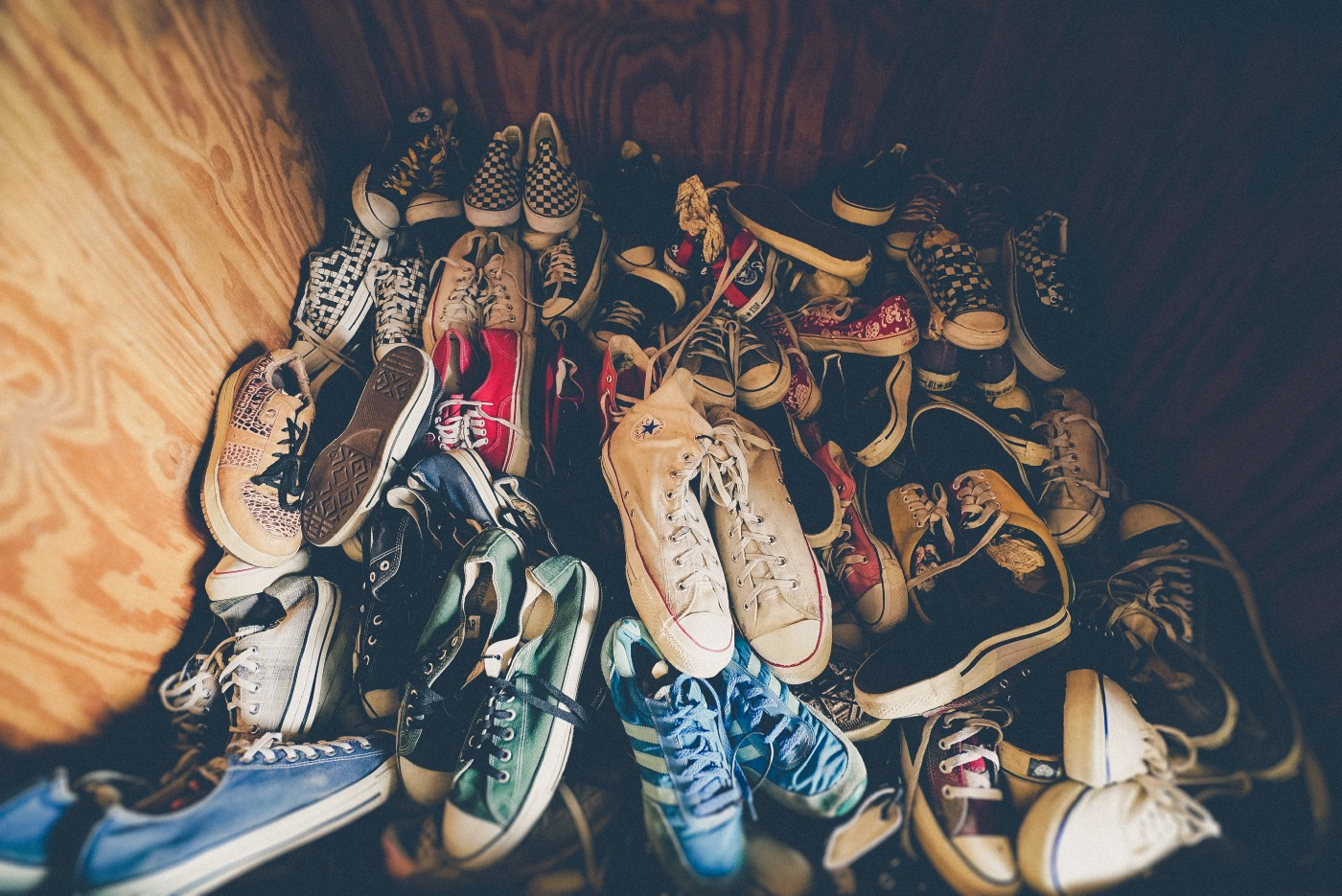 A wooden cubby filled with dozens of disordered shoes, each varying in color, shape, and position.