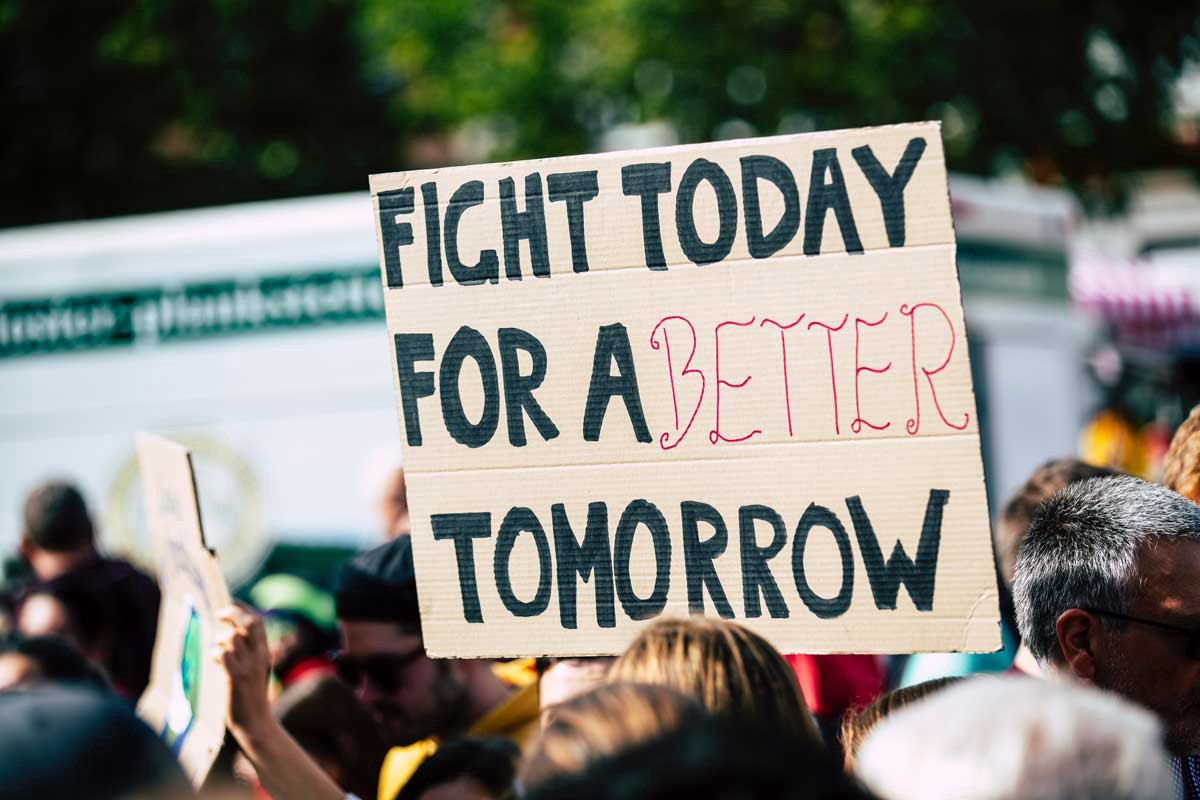 """a cardboard protest sign in a crowd that says """"Fight today for a better tomorrow"""""""