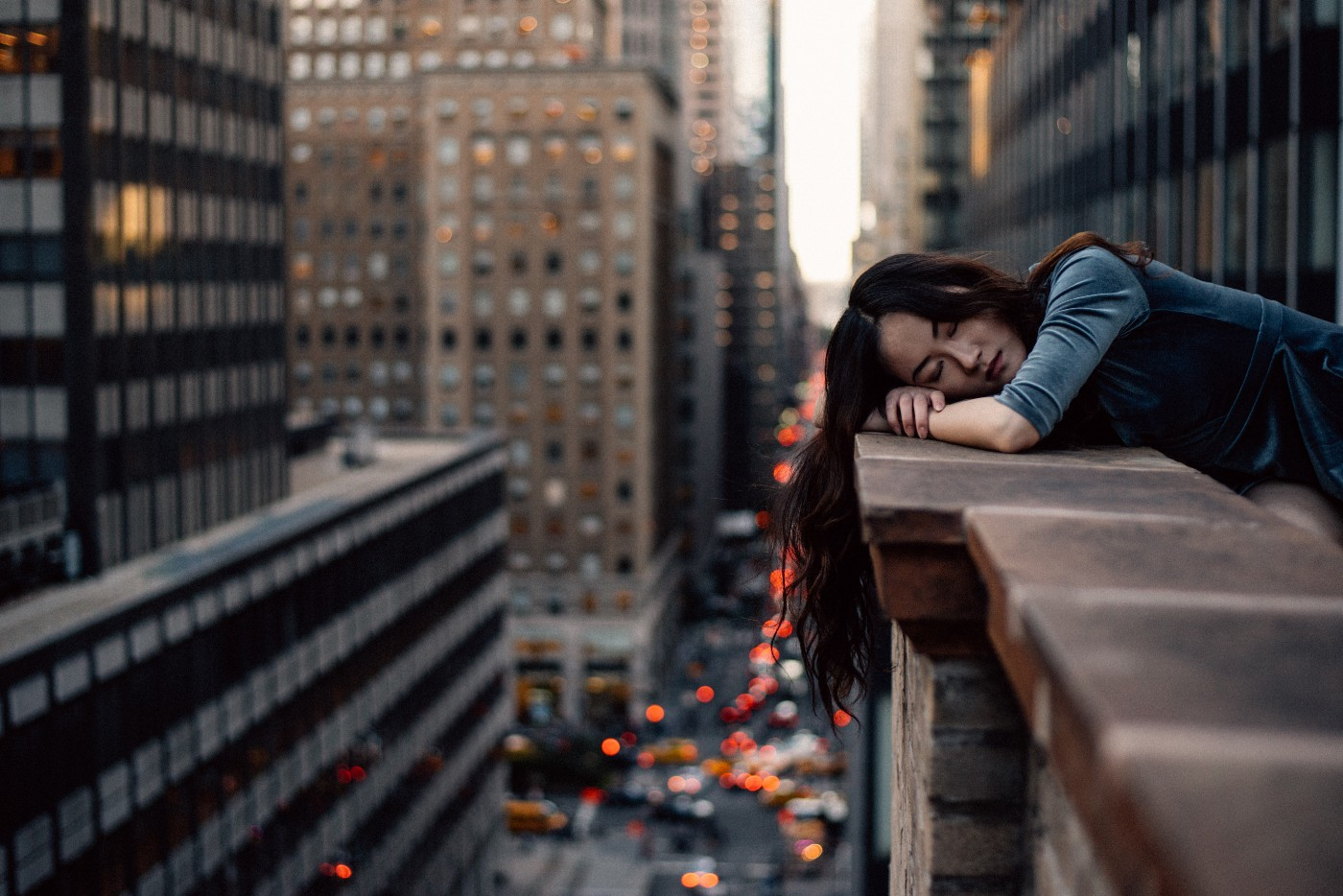A woman resting her head wearily on a balcony overlooking a city.