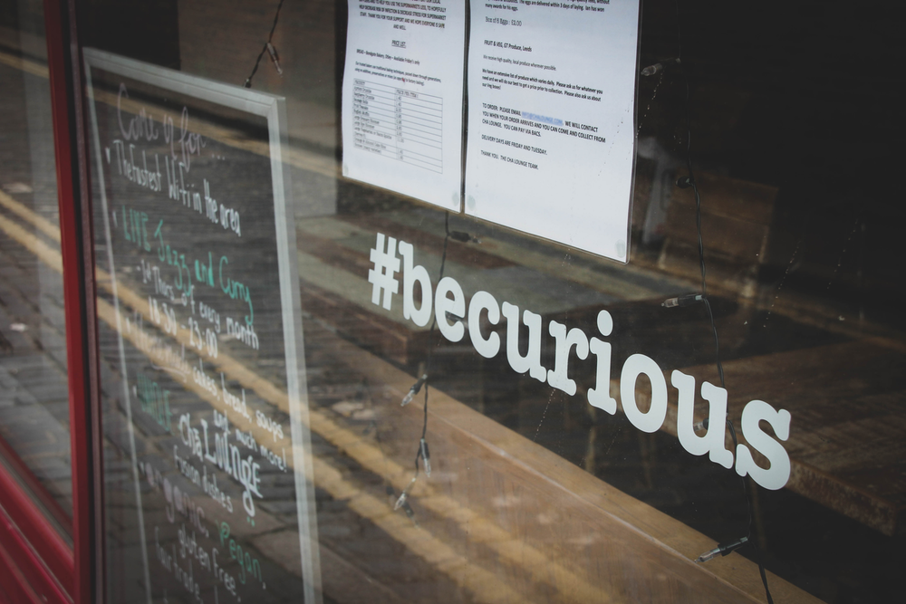 """Store window with the hashtag """"be curious"""" on the window"""