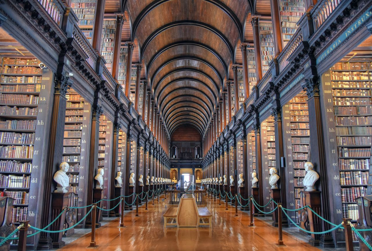 A long view down The Old Library's symmetrical central corridor, with tall bookshelves towering on either side.