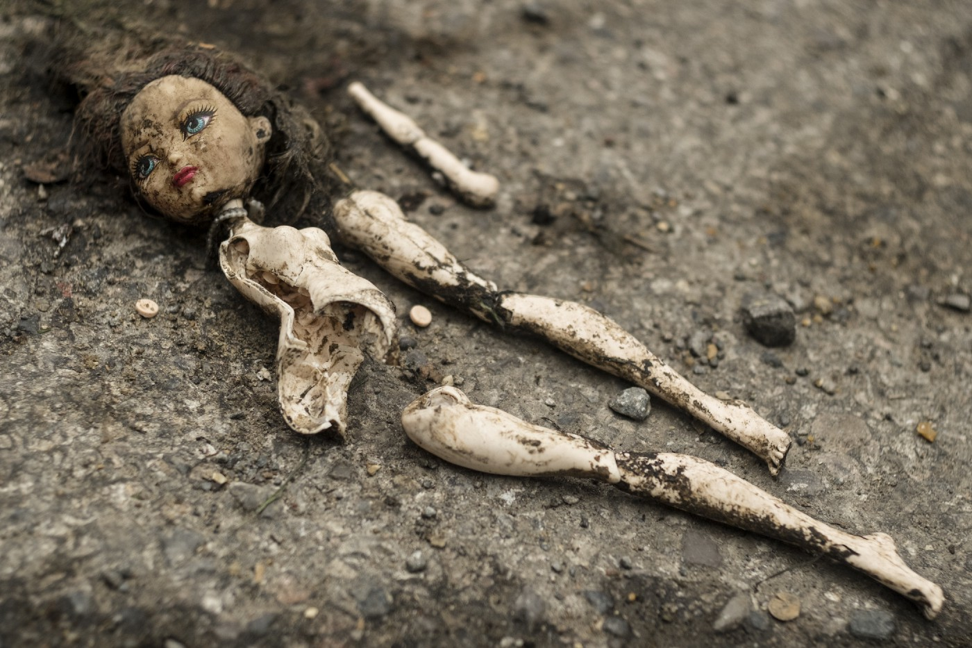 A broken doll in the dirt.
