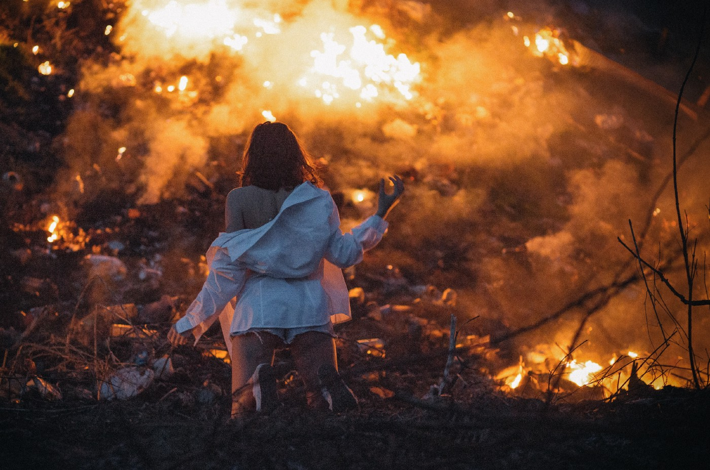 Woman kneeling in front of an apocalyptic fire scene.
