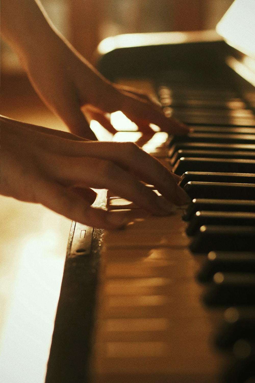 Female hands playing a piano.