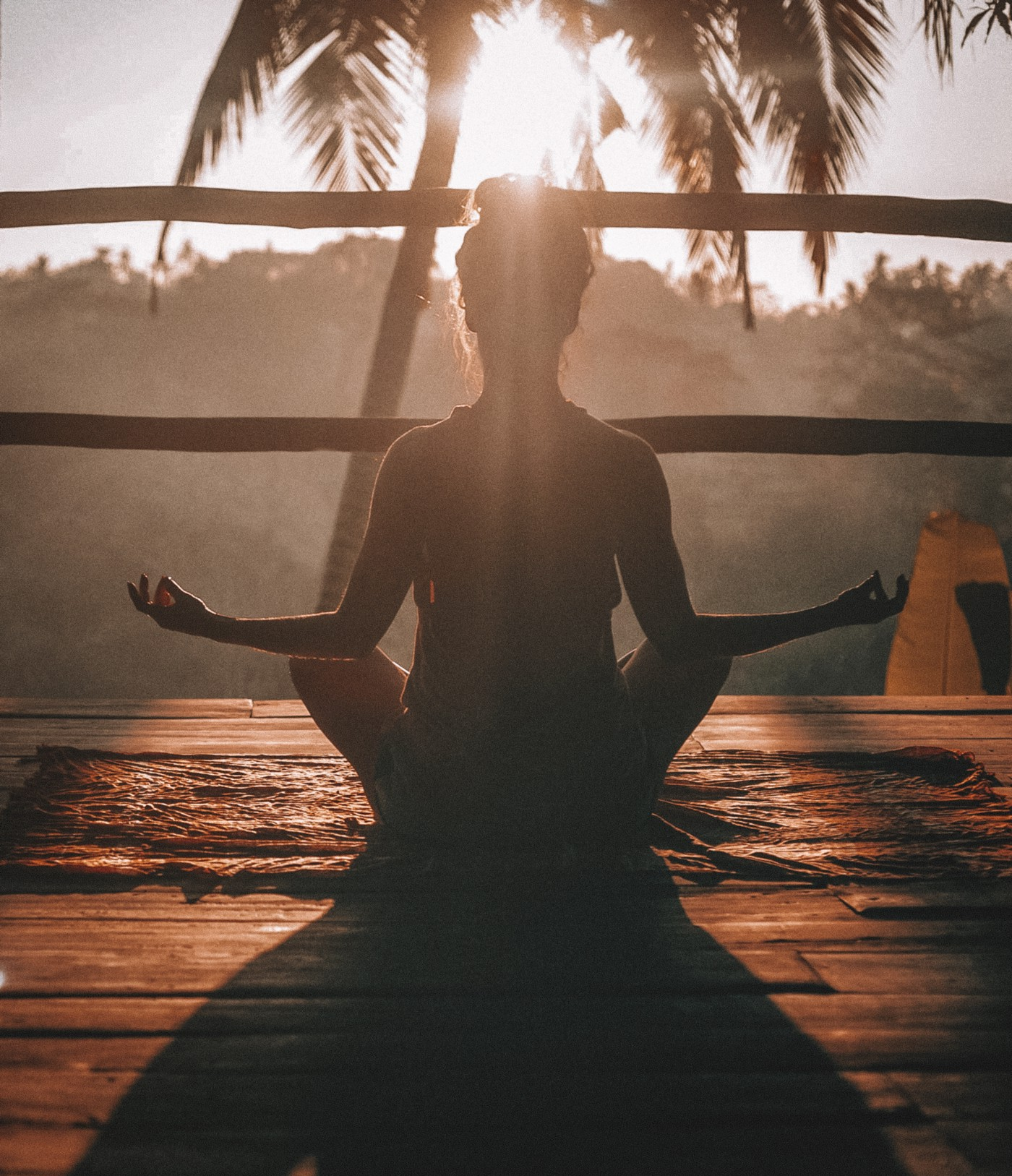 Person meditating in front of a slowly descending sun.