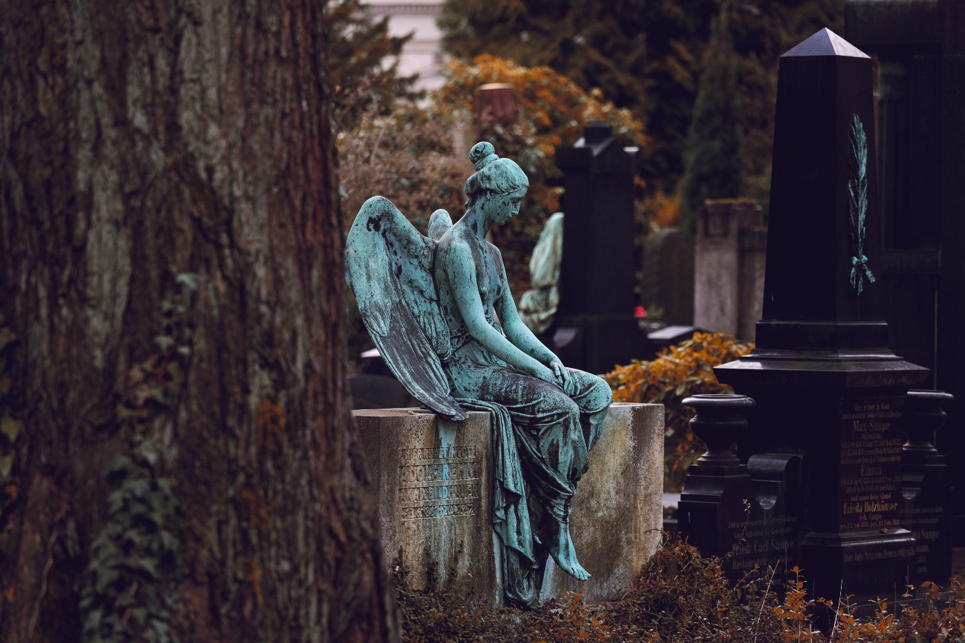 Statue of an angel sits on a tombstone in a cemetery — head bowed down, hands in lap.