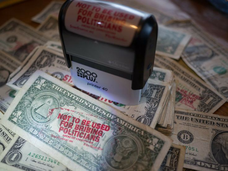 riottech: a self inking stamp sitting on a heap of bank notes. The stamp text says it's not to be used for bribing politicians.