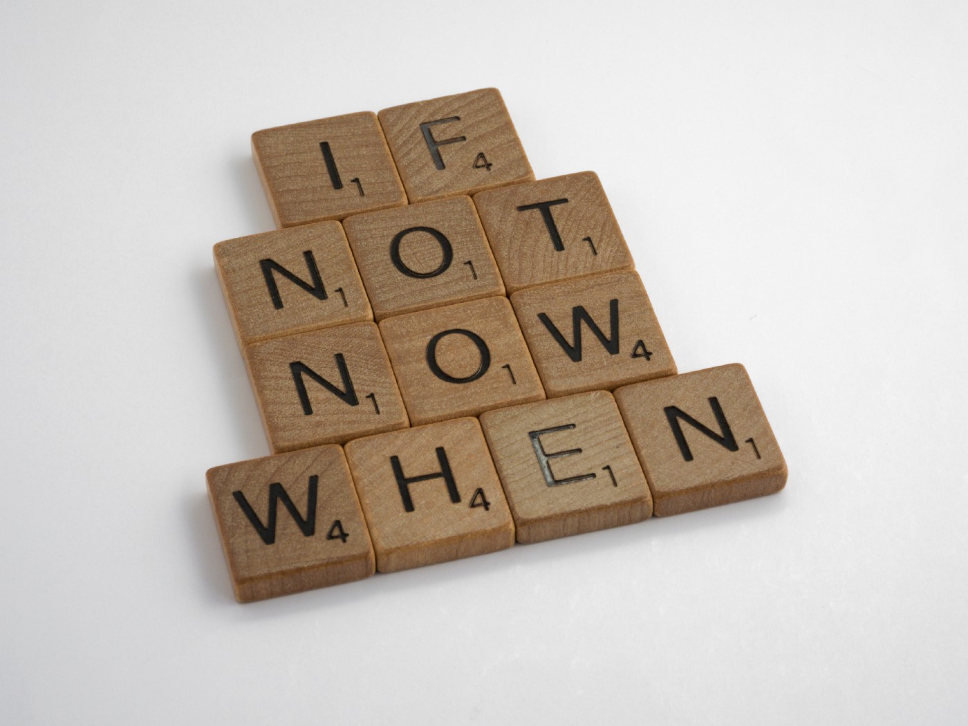 """Several scrabble letters arranged to read: """"if not now, when""""."""