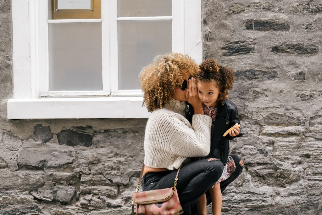 Mother whispering a secret to her daughter | photo by Sai De Silva on Unsplash