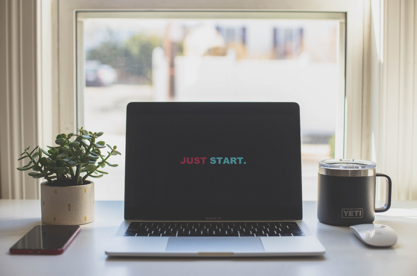 "Laptop screen that reads ""JUST START."""