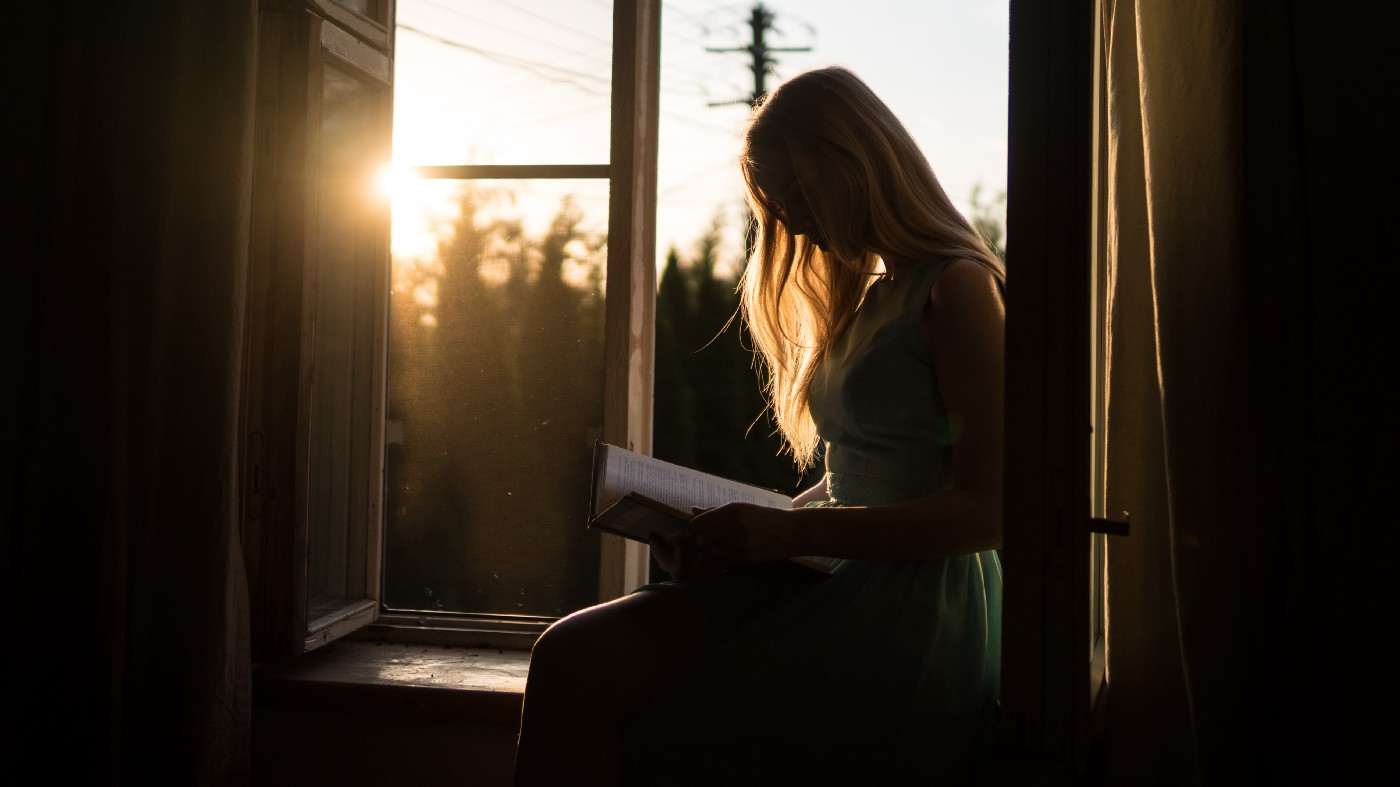 The silhouette of a woman sitting on a windowsill reading a book. Golden sunlight is coming in through the open window.