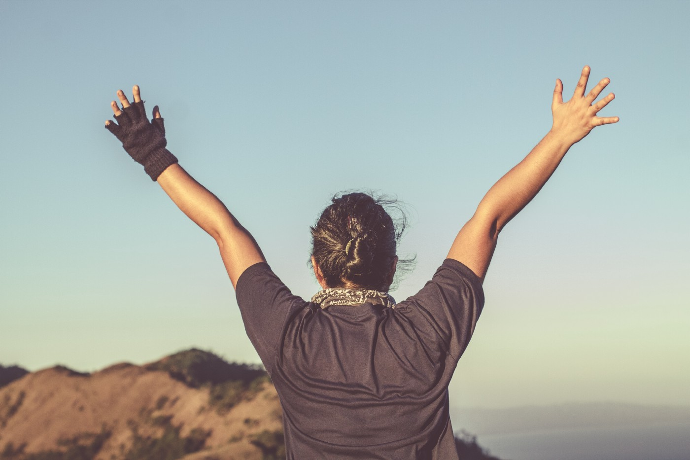 A woman is facing the horizon with her arms held high in a sign of victory