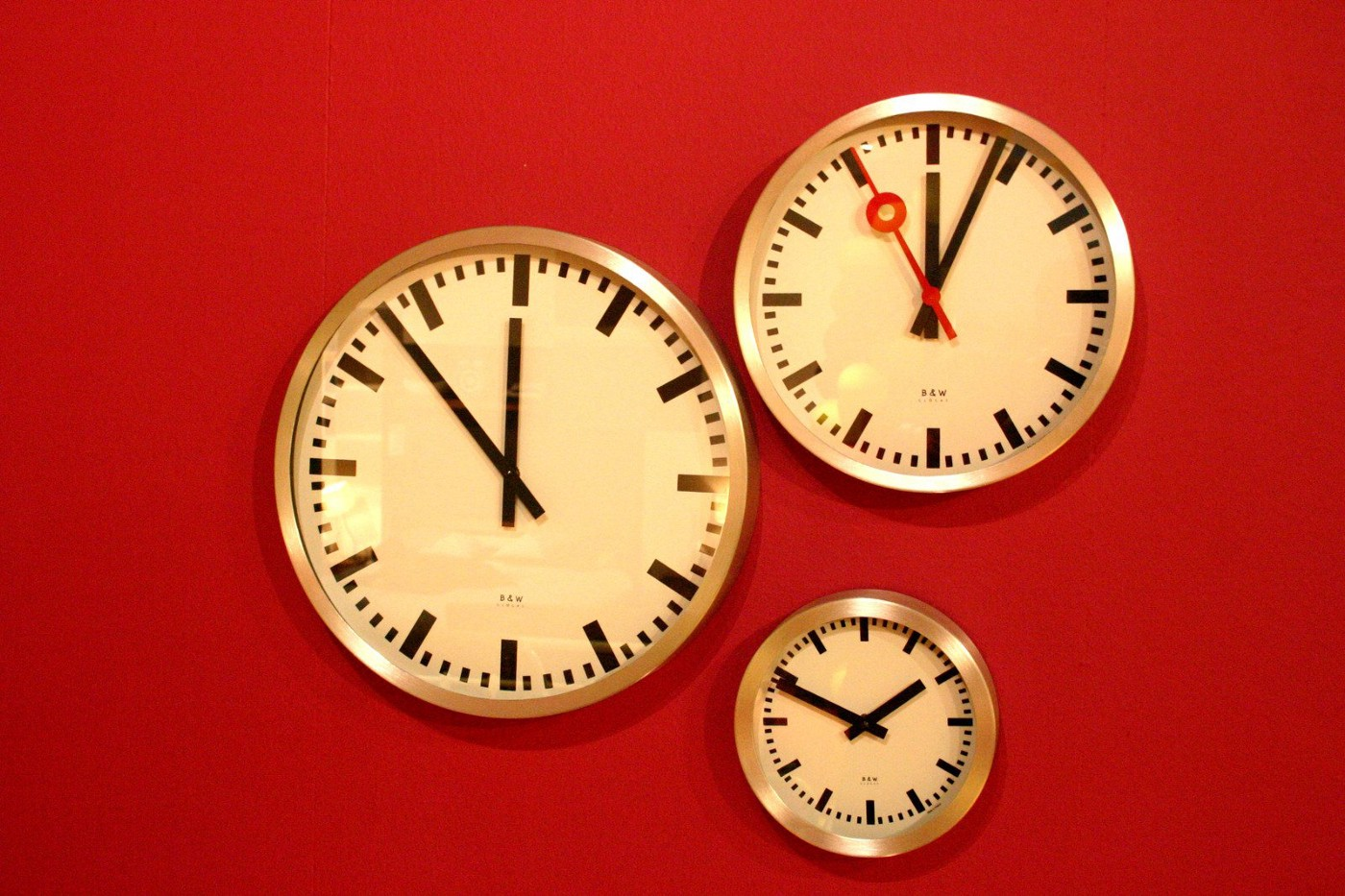 Three analog clocks of various sizes positioned against a red background.