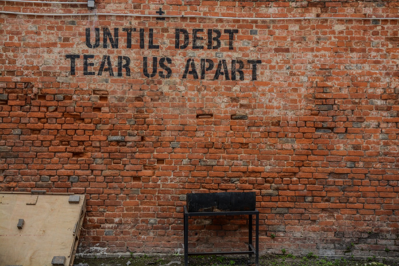 """Picture of a orange-red brick wall with a sign that reads """"Until debt tear us apart""""."""