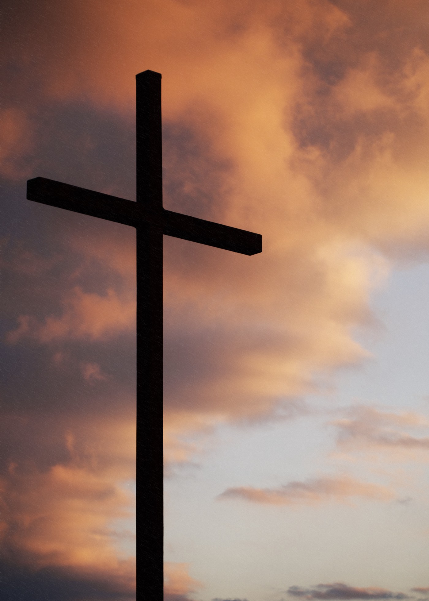 Backlit cross against peachy and gray sunset clouds