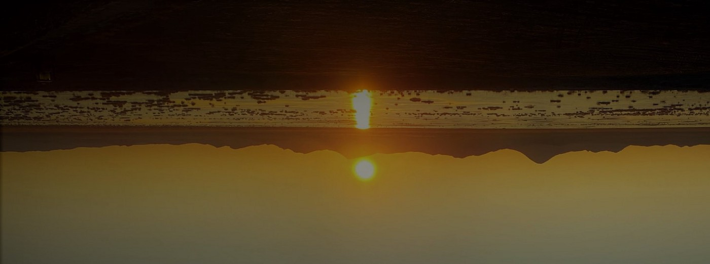 An upside down picture of a sunset reflecting in water. The elongated reflection and sun look like an exclamation point.