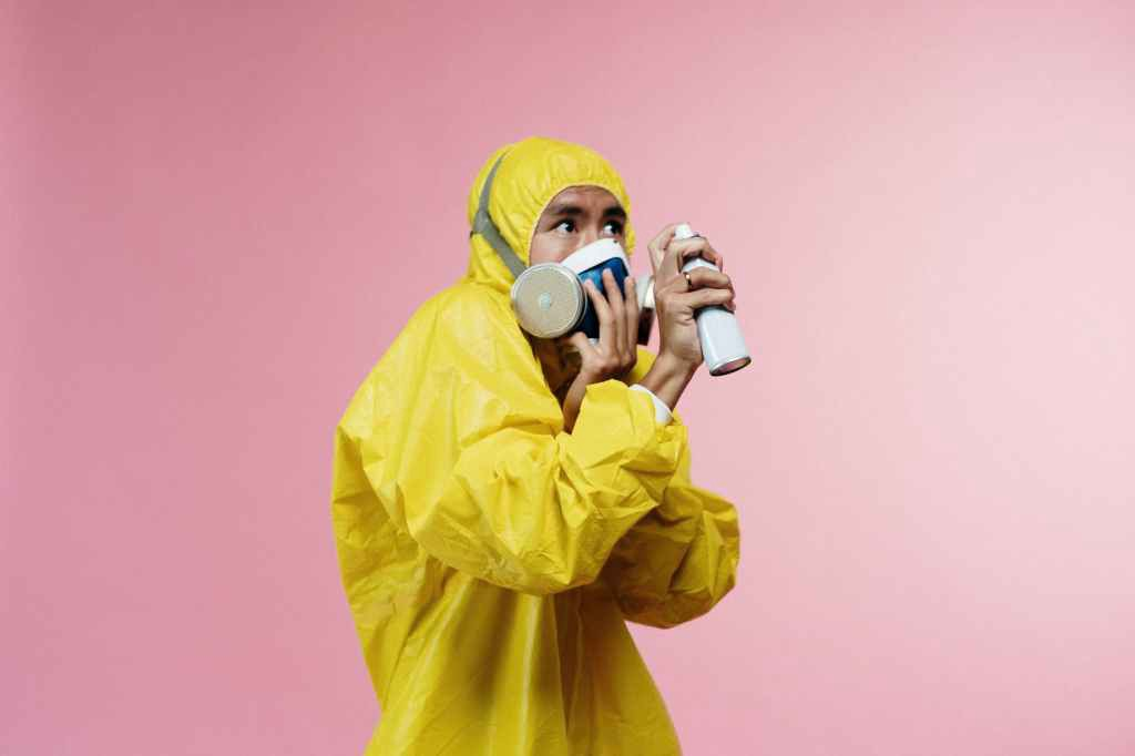 Man in yellow hazard suit with mask and spray can.