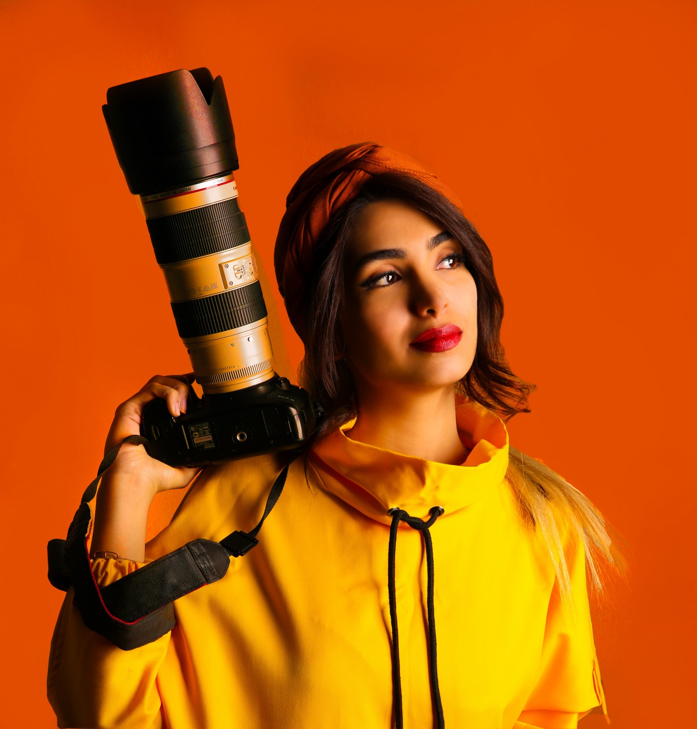 A woman in a yellow jacket and red head scarf holding a camera with a large lens in a vibrant reddish orange background