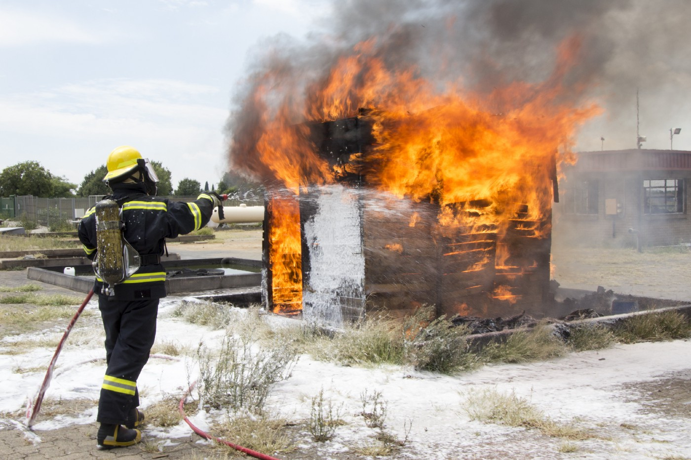 A firefighter points a hose at a vehicle engulfed in flames.