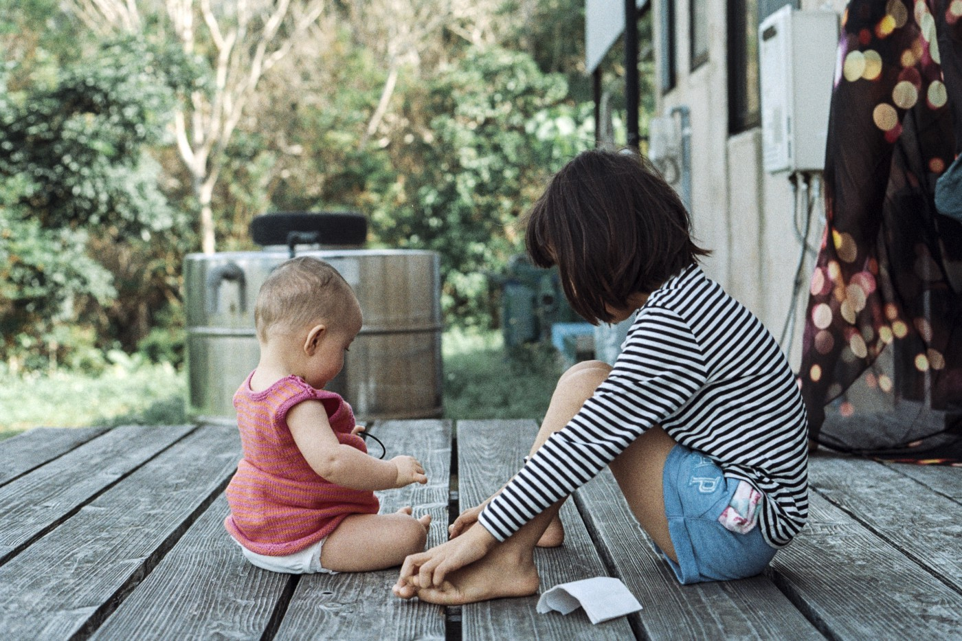 Baby with older girl sitting on porch with heads looking down