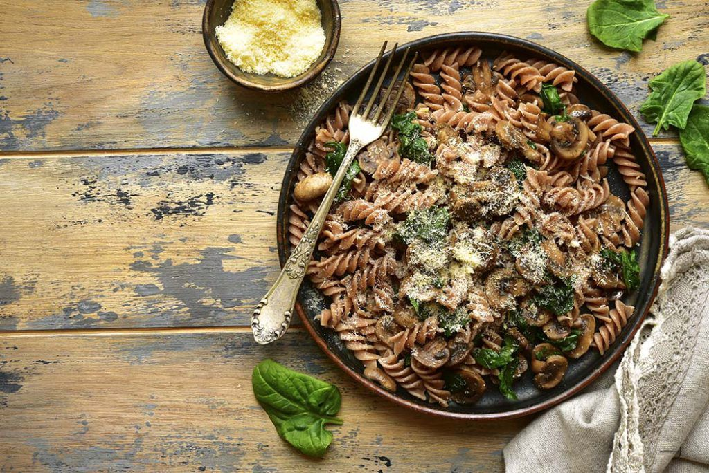 Spinach and mushroom whole wheat pasta topped with freshly grated parmeson cheese in a brown bowl, on a wooden table.