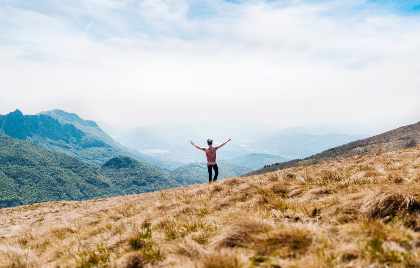 Person with both arms raised looks out into a foggy mountain range