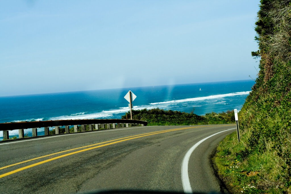 Curving road with blue sky and ocean ahead, view from interior of car