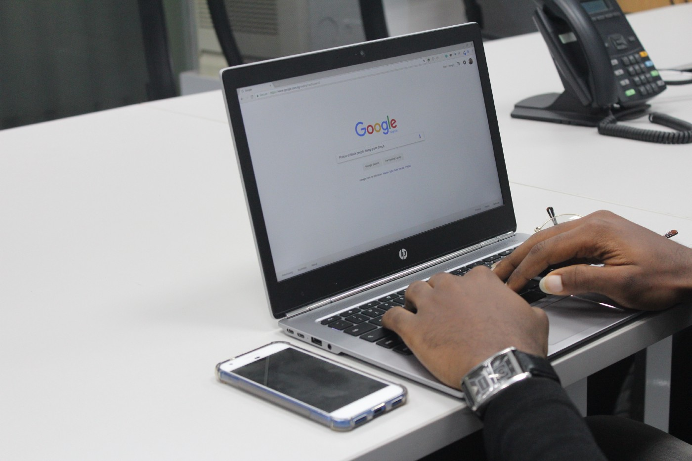 Google, shown on the screen of a laptop. A man wearing a watch. There is an iPhone on the table.