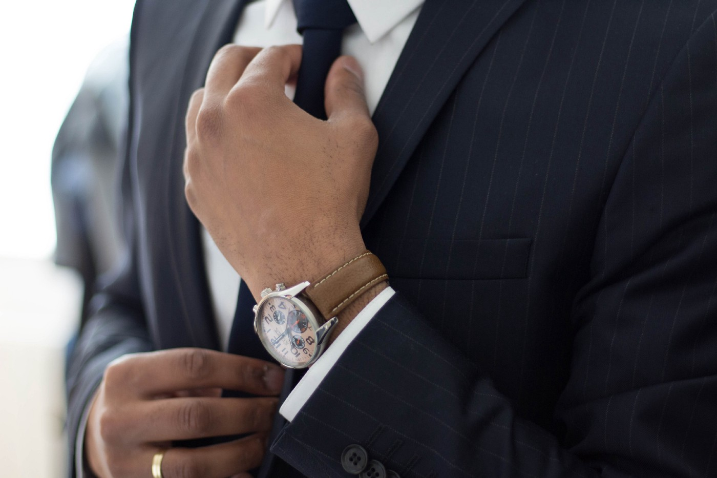 A man in a suit tightens his tie. He's wearing an expensive watch on his wrist.