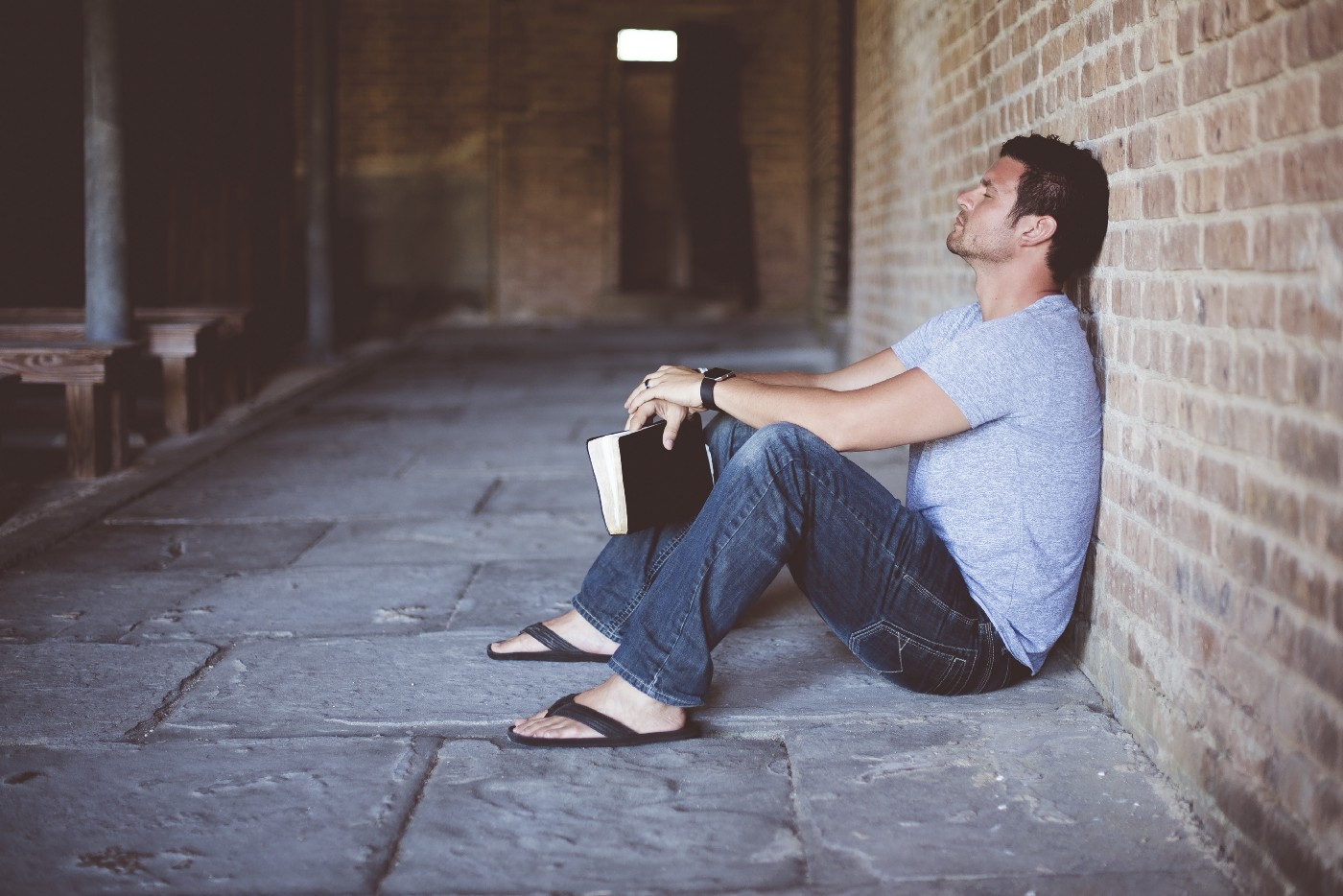 Man sitting against a wall with a book in his hand. He looks lost and mentally drained.