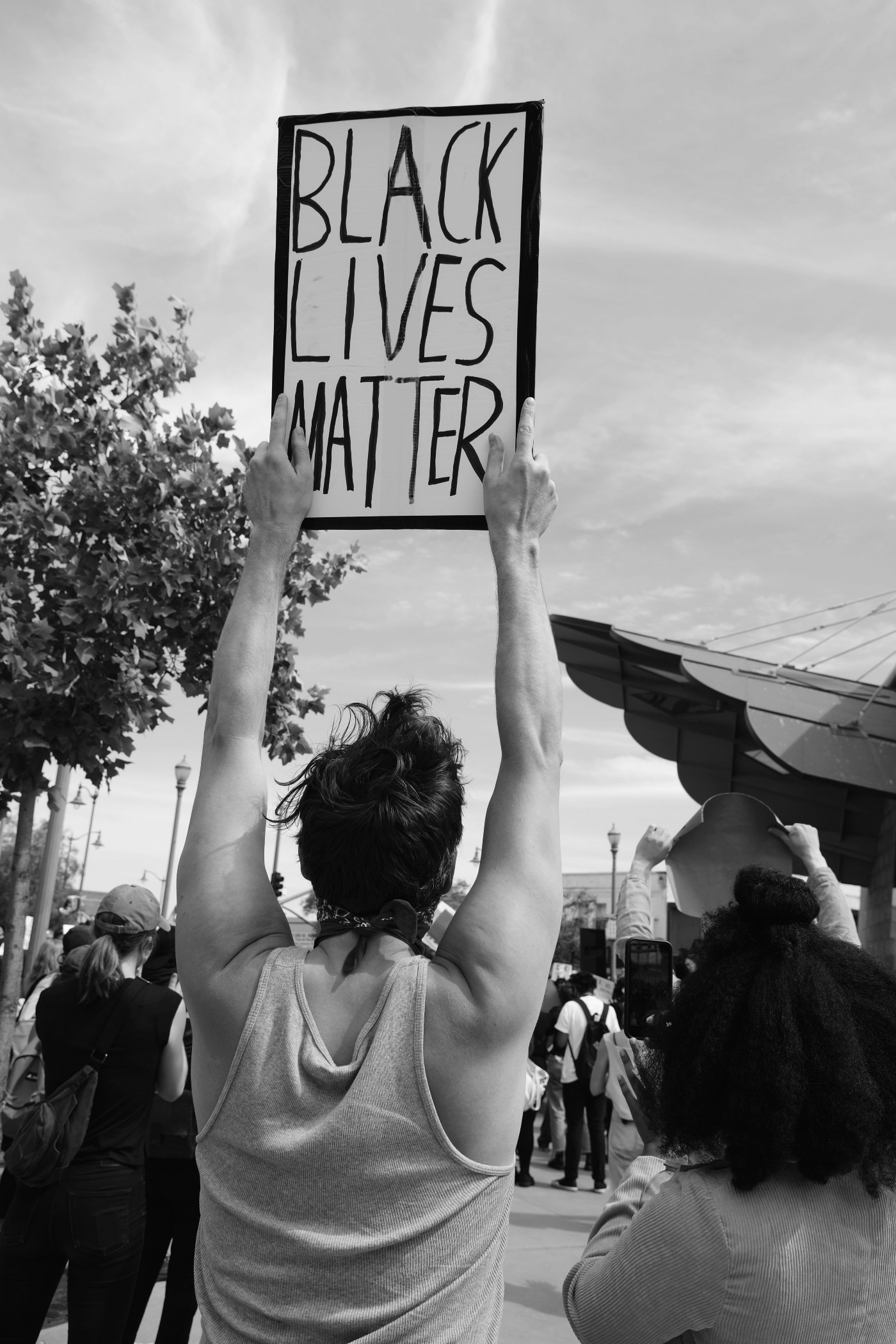 Person identified as white holding Black Lives Matter sign
