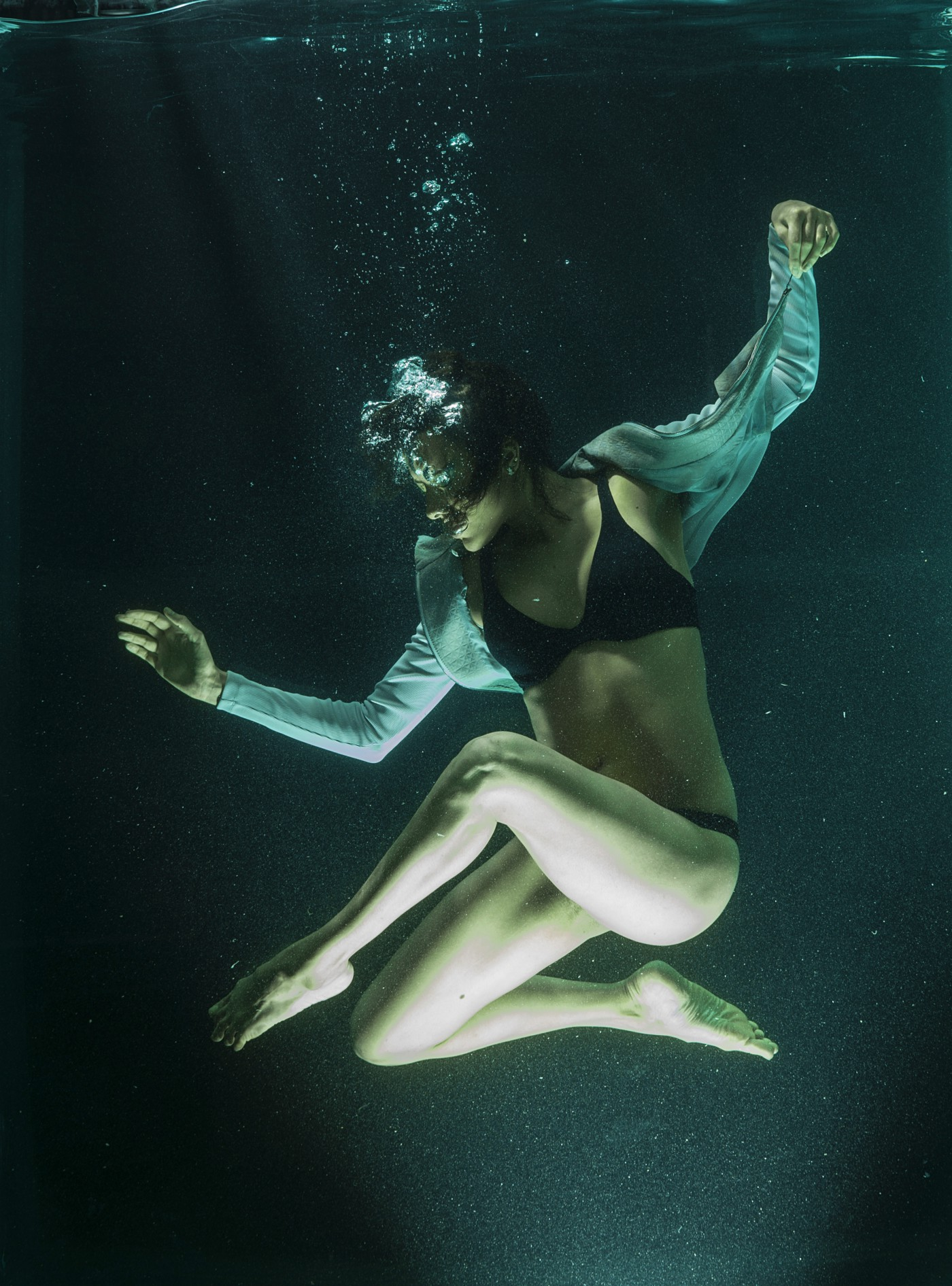 Underwater. Model poses in a dancer-like position with arms outreached and legs in a zigzag shape. Bubbles erupt from her mouth, slightly obscuring her serene expression.