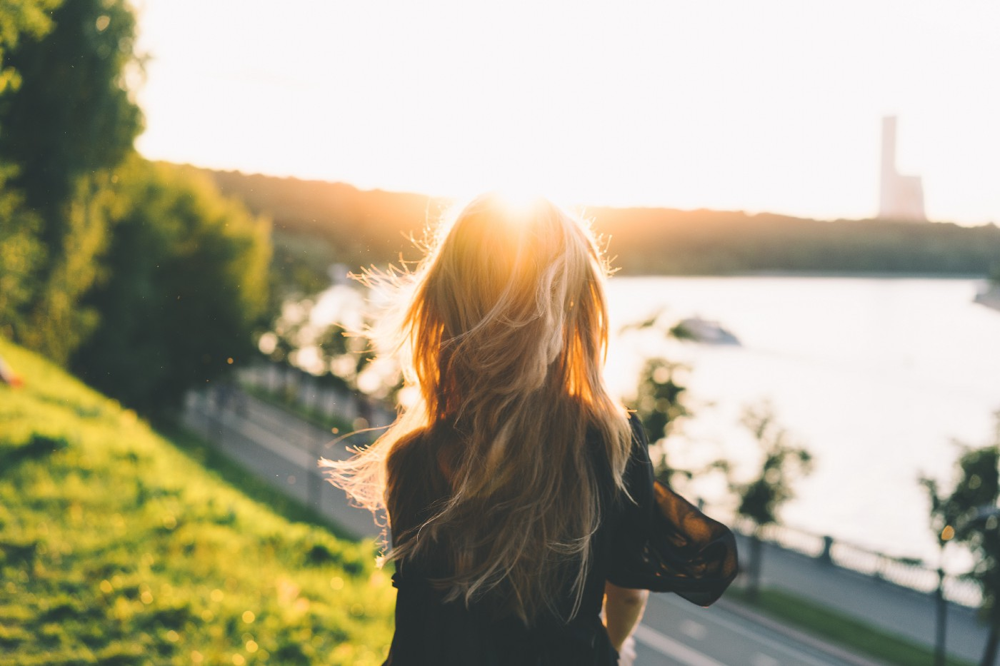 A woman stares out at the sunrise view of a boulevard by the water's edge, a lighthouse in the distance.