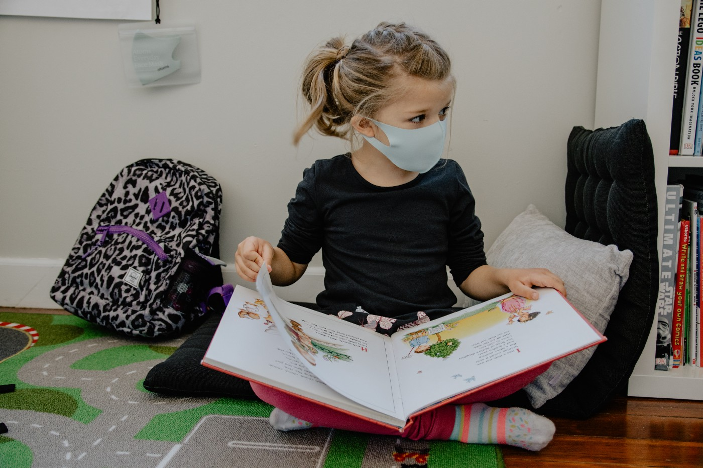 A small child (girl) studying book in school library