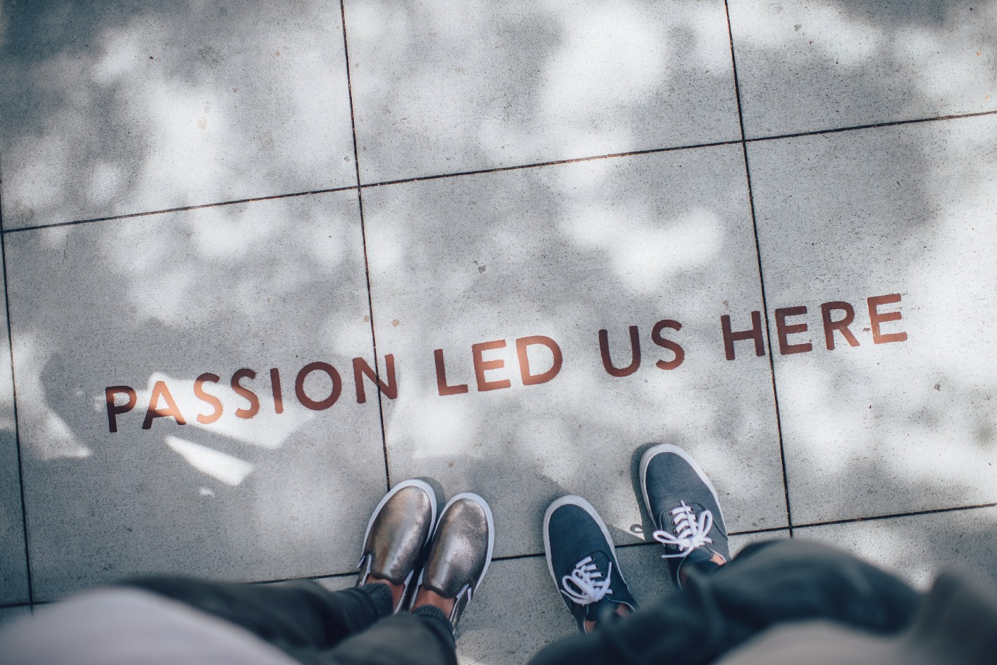 "Shoes and legs of two people are visible with text printed on floor ""Passion Led Us Here"""