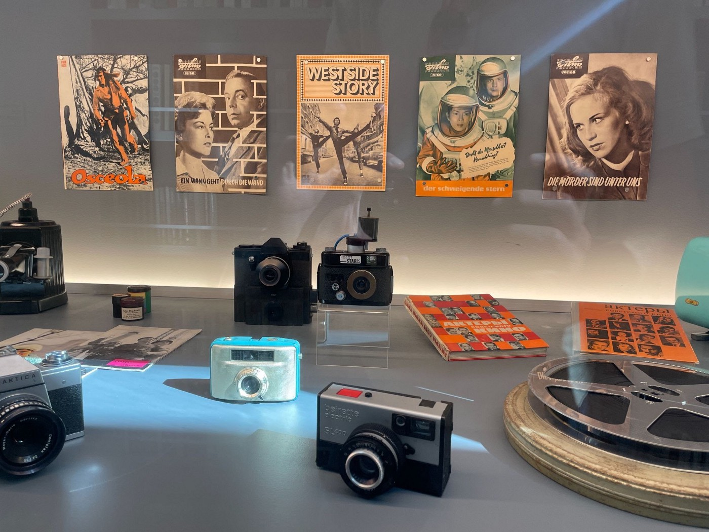 A display featuring a collection of cameras, film, and Polish zine-like leaflets from the Cold War era.