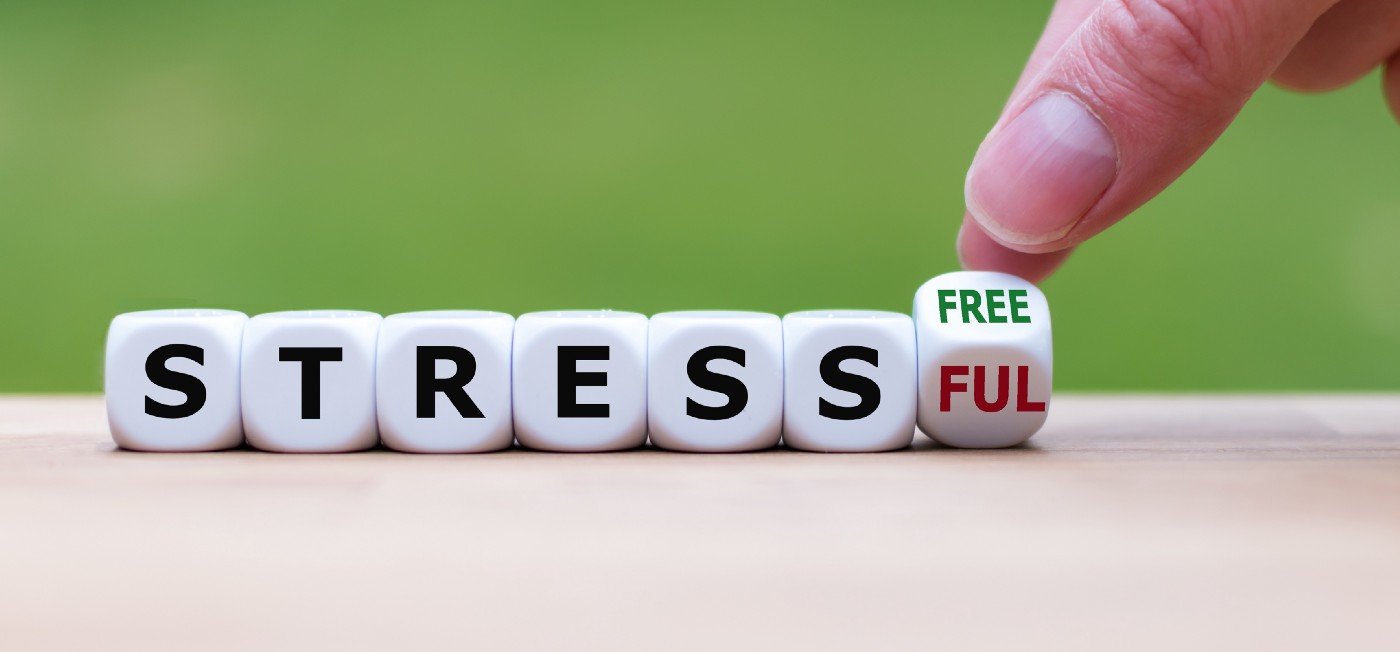 Die with the letters STRESS and FREE/FUL being spelt. A hand is holding the FREE/FUL part to indicate that being stress-free or stressful is an option we have. Stress hampers creativity.