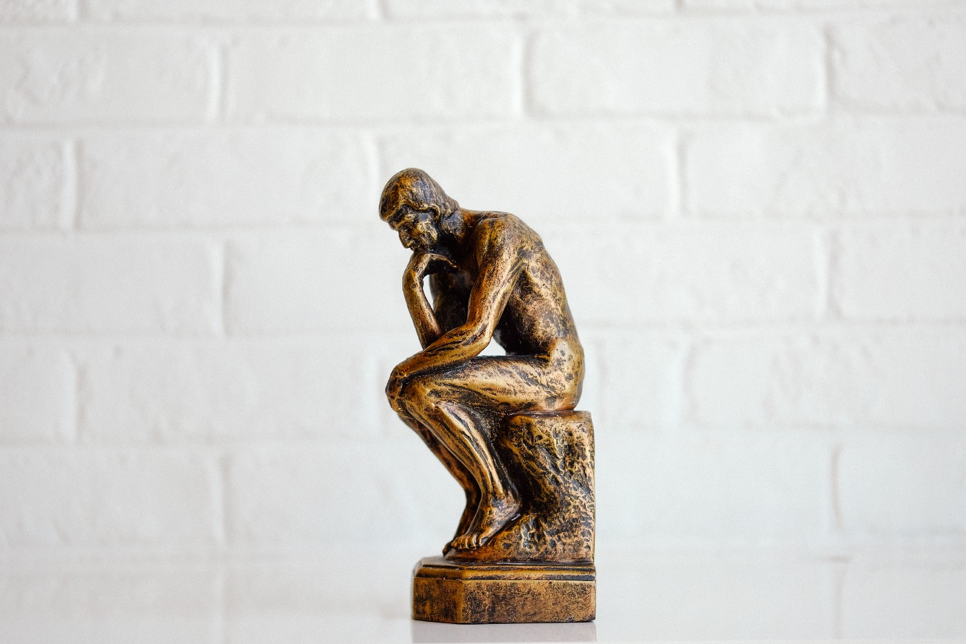 the thinker statue in kitchen against the wall stoic