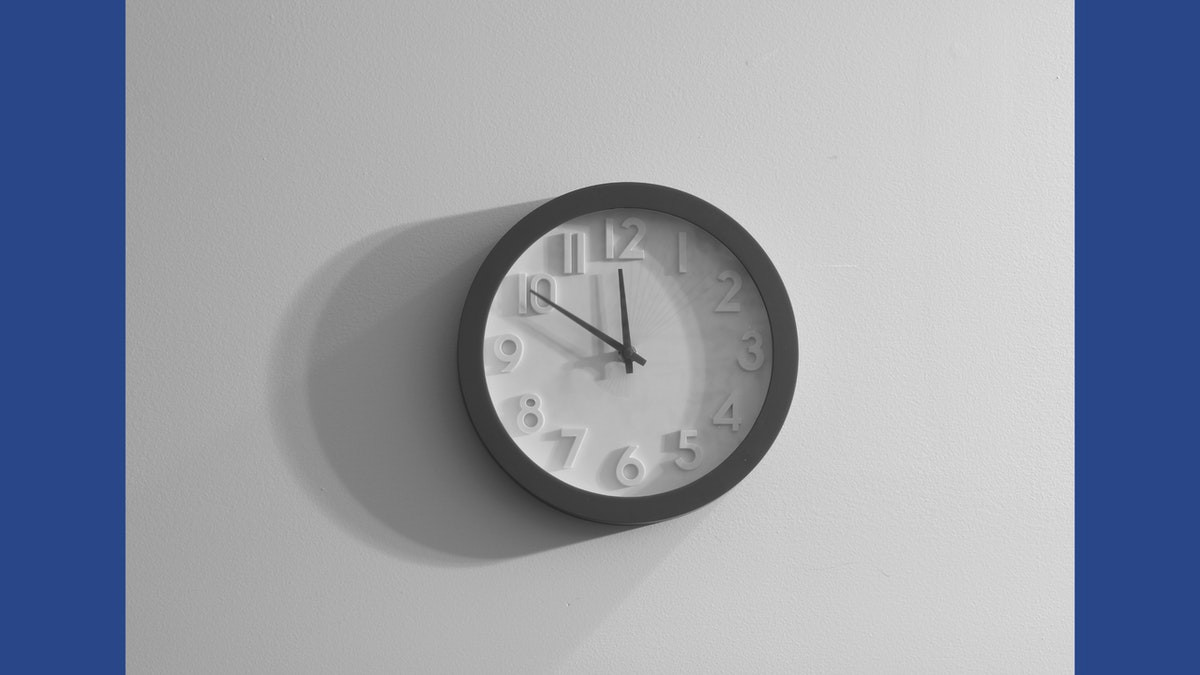 Image of a clock against a pale, grey wall.