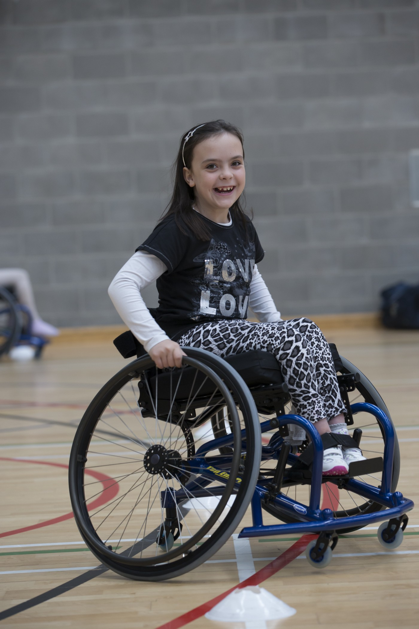 beautiful young child wearing a love tee shirt in a wheelchair