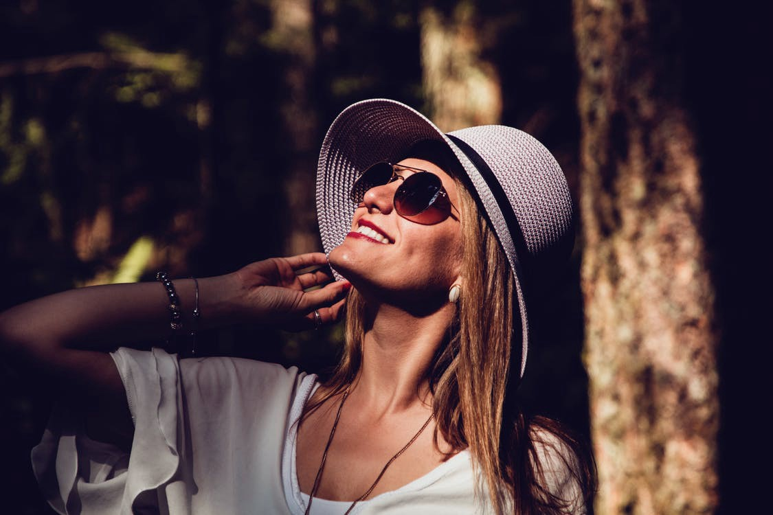 A woman wears a white shirt, sunglasses, and a floppy hat. She smiles and rests her hand under her chin while looking up at the sun. #happy #confident #beautiful #sunlight