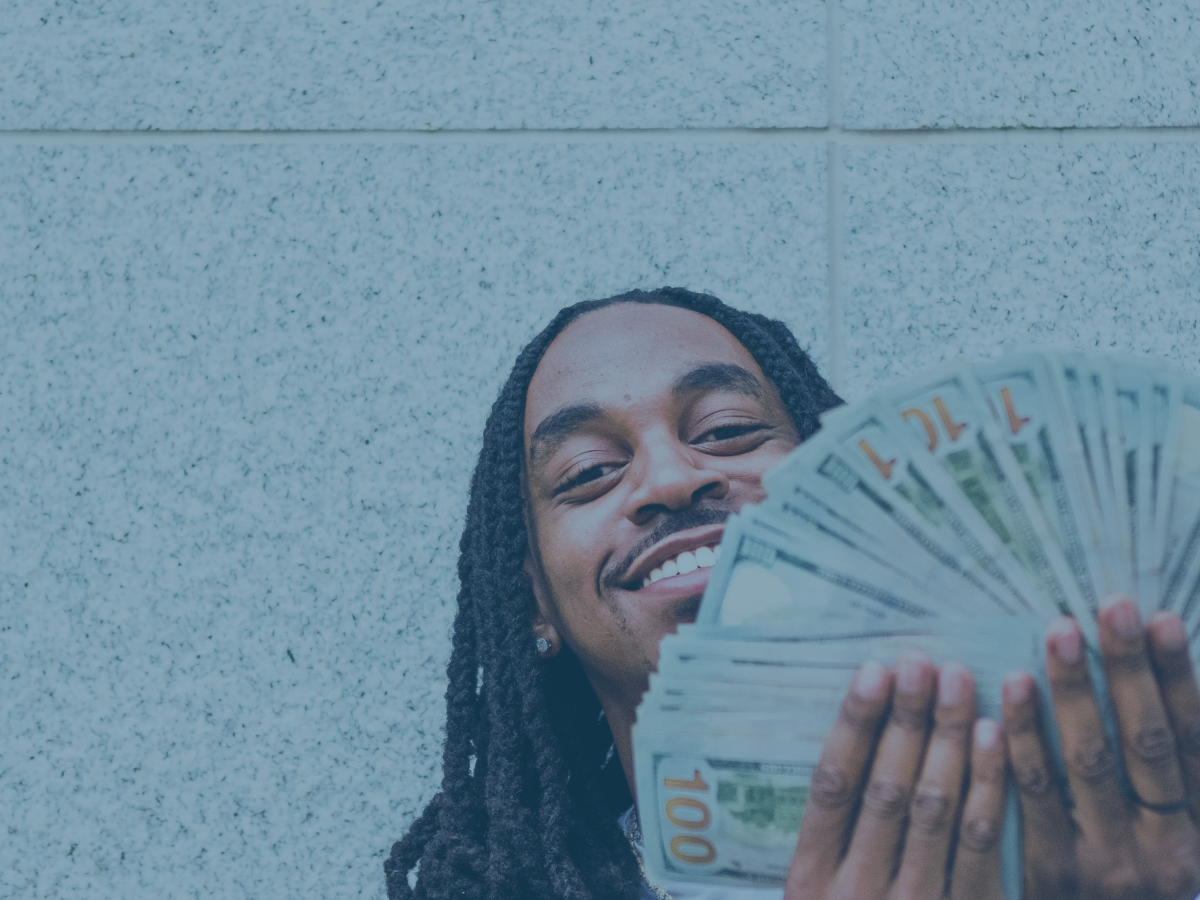 Image shows a man happily fanning many $100 dollar bills.